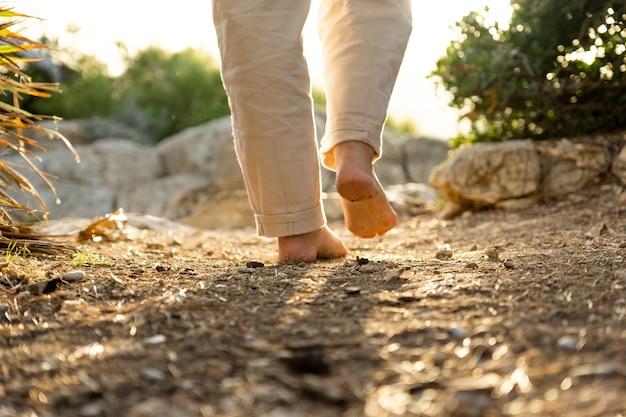 Piedi nudi che camminano sulla terra con una splendida luce del tramonto