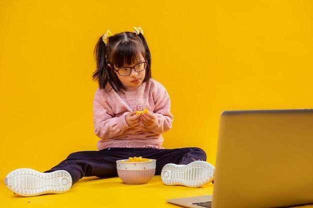 Sul pavimento nudo. piccola signora interessata con sindrome di down che mangia patatine e guarda i cartoni animati sul laptop