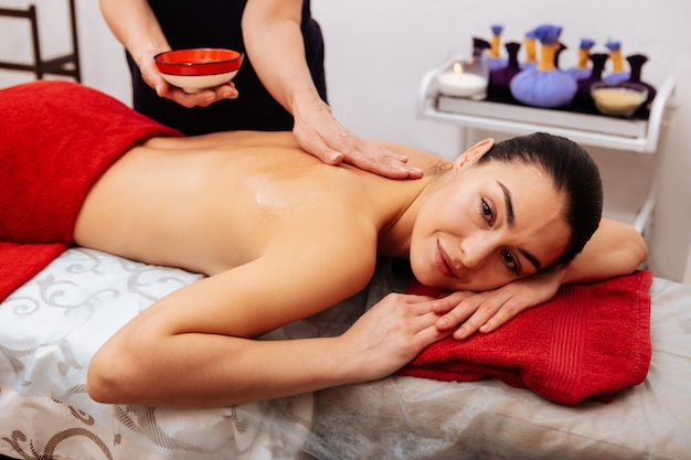 Mani nude. sorridente donna dai capelli lunghi positiva che riposa sul lettino da massaggio mentre il maestro aggiunge più olio sulla schiena