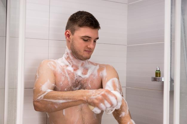 Uomo nudo che si strofina una spugna da bagno in schiuma mentre si trova in una cabina doccia con porte in vetro trasparente in bagno