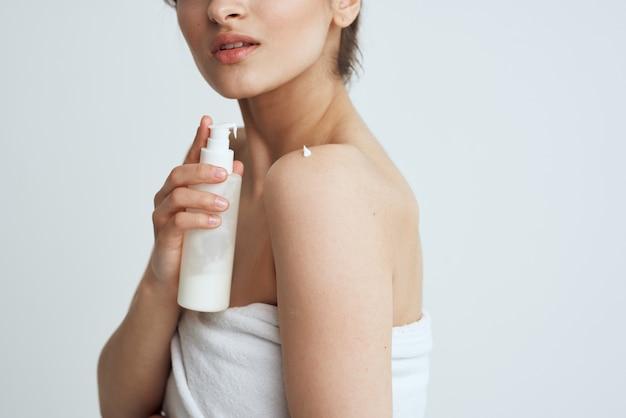 Lozione asciugamano bianco a spalle nude per la cura della pelle