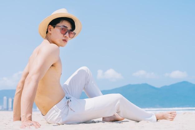 Barebacked giovane uomo asiatico seduto sulla sabbia e guardando il mare