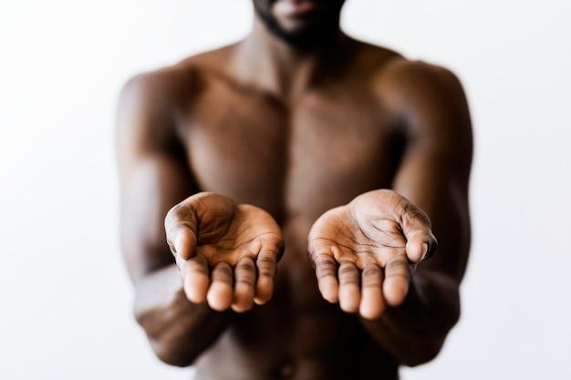 Uomo a petto nudo che mostra qualcosa sul modello di pubblicità dei palmi delle mani