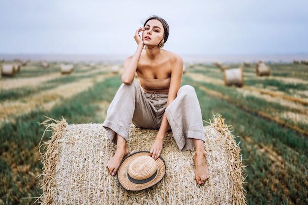 Bruna a piedi nudi in pantaloni di lino e spalle nude seduto su balle di fieno in una calda giornata d'autunno. sguardo della donna dietro di lei c'è un campo di grano