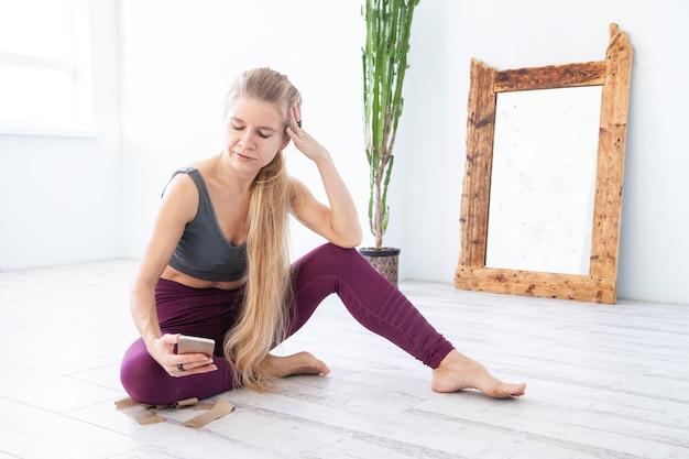 Atleta a piedi nudi in abbigliamento sportivo che riposa sul pavimento e naviga su smartphone durante la pausa in allenamento a casa