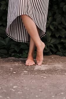 Piedi femminili a piedi nudi sul primo piano del marciapiede. stile di vita