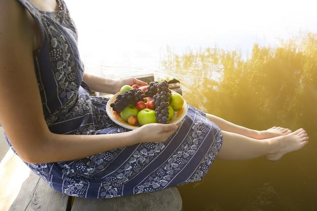 La ragazza a piedi nudi è seduta vicino al fiume in abito vintage blu. la donna sta tenendo il piatto con la frutta. piatto rustico. concetto di stile di vita sano cibo vegetariano. ponte di legno. vibrazioni estive.