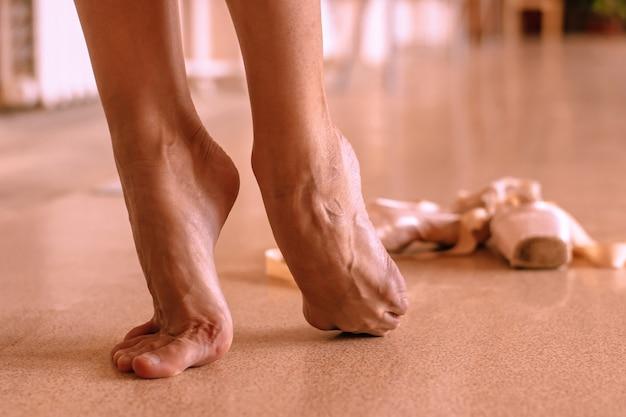 Le gambe scalze di una ballerina che balla nella classe di balletto