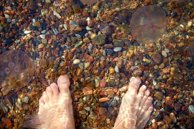 Piedi maschili a piedi nudi sulla spiaggia con ciottoli