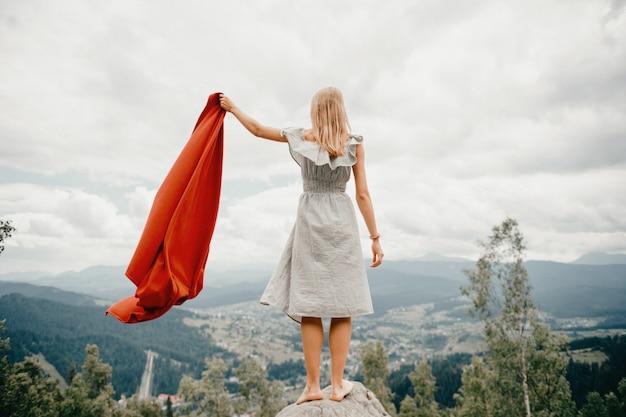 La donna scalza sta alla pietra, agitando la coperta rossa