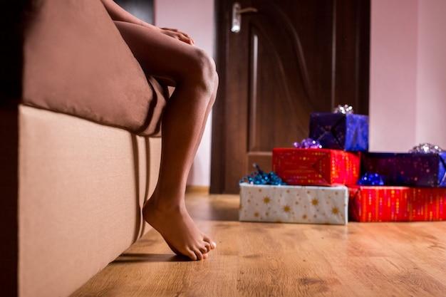 Bambino scalzo seduto accanto a regali regali vicino al letto dei bambini afro svegliati il suo natale alzati un...