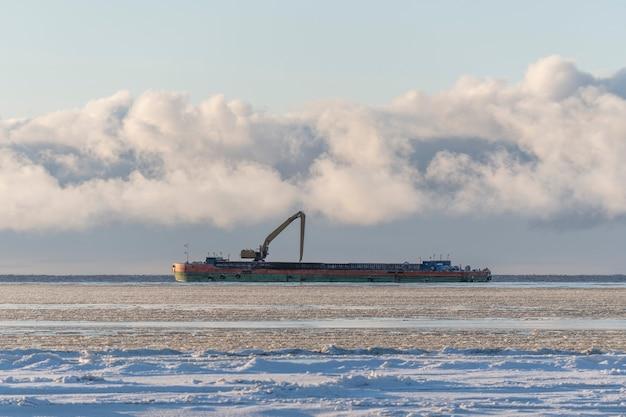 Chiatta con escavatore nel mare artico in inverno. nave materiale di scavo da un ambiente acquatico.