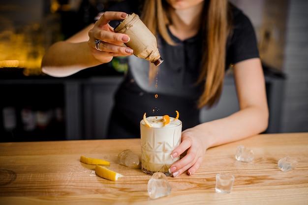 Il barista aggiunge un topper al cocktail con la buccia d'arancia