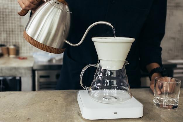 Barista che prepara il caffè, metodo versato, caffè americano