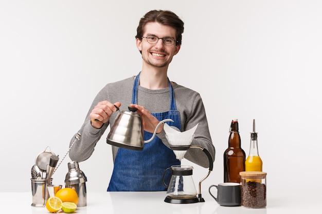 Concetto di barista, lavoratore barista e barista. il ritratto di giovane uomo barbuto allegro amichevole nel grembiule sorride al cliente mentre versa l'acqua dalla teiera per produrre il caffè del filtro