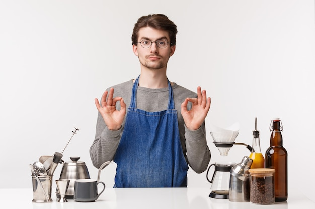 Concetto di barista, lavoratore barista e barista. il ritratto di giovane ragazzo caucasico dall'aspetto serio in occhiali e grembiule, mostra ok segno eccellente, è d'accordo o garantisce che il cliente apprezzerà il caffè