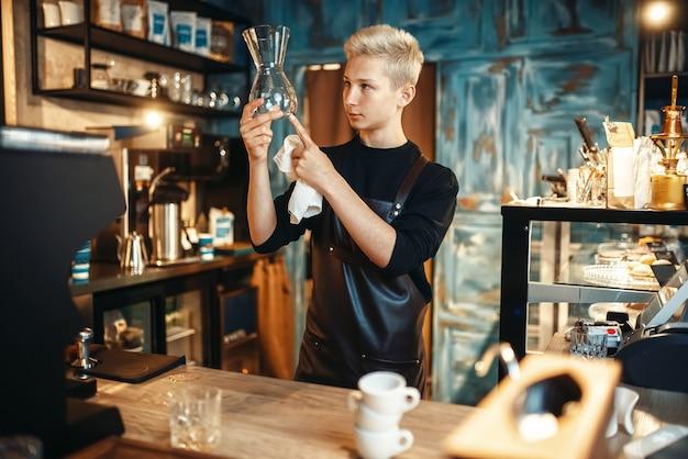 Il barista controlla i piatti puliti dopo aver preparato il caffè