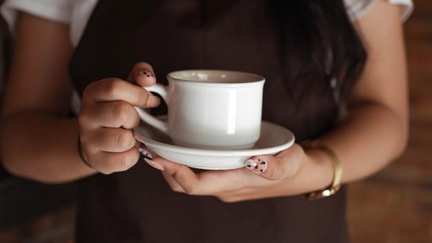 Barista femminile che tiene tazza di caffè al caffè