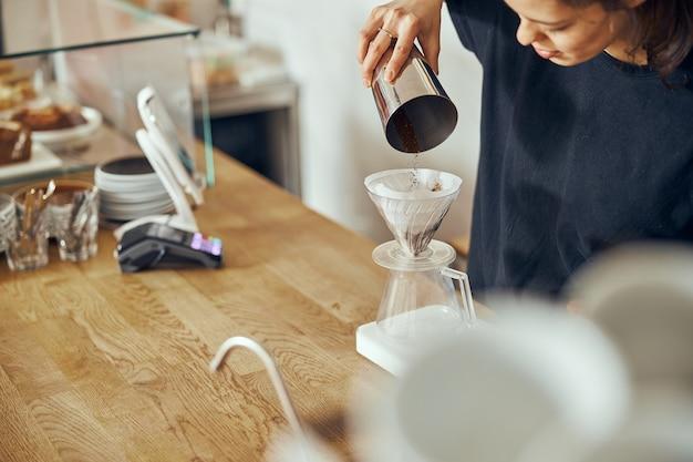 Barista femminile sta preparando una deliziosa polvere di caffè mattutina appena macinata nel filtro del caffè.