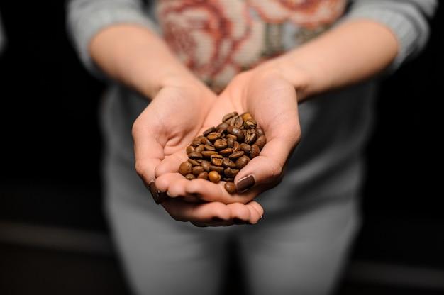 Ragazza barista con in mano una piccola manciata di chicchi di caffè