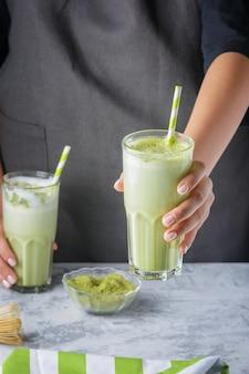 La ragazza di barista dà il tè verde del latte di matcha. foto ritagliata. bevanda sana da vicino