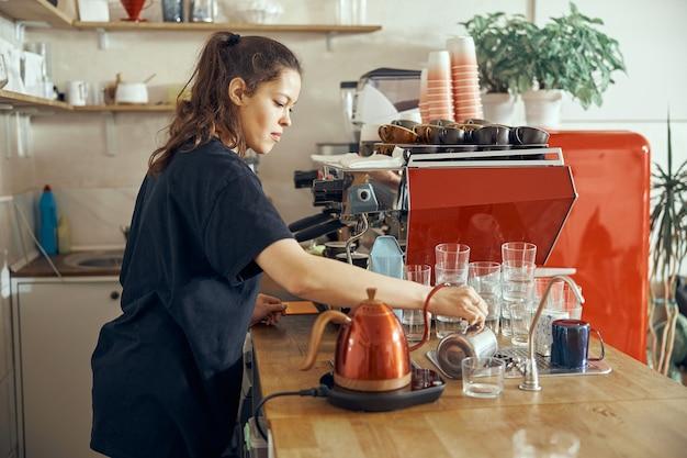 Barista che dà ordine al cliente presso la caffetteria alla moda. versare l'acqua in un bicchiere.