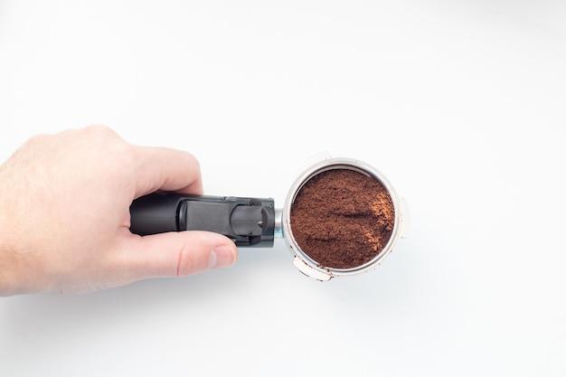 Barista che tiene il titolare del caffè con caffè macinato su bianco