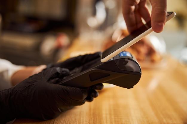 Barista che tiene in mano una macchina per i pagamenti mentre il cliente paga tramite smartphone nella caffetteria
