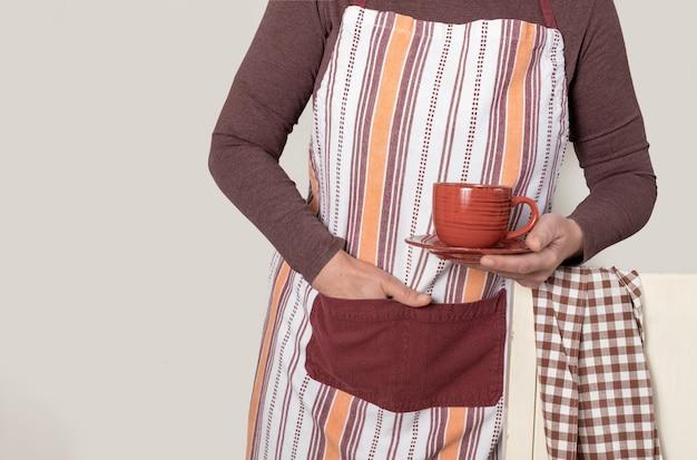 Barista che tiene tazza di caffè o tè rosso su sfondo bianco