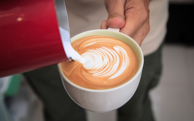 Il barista fa arte del latte. latte della tazza di caffè in caffetteria