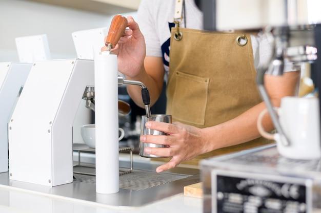 Barista che fa una tazza di caffè dalla macchina del caffè nella caffetteria