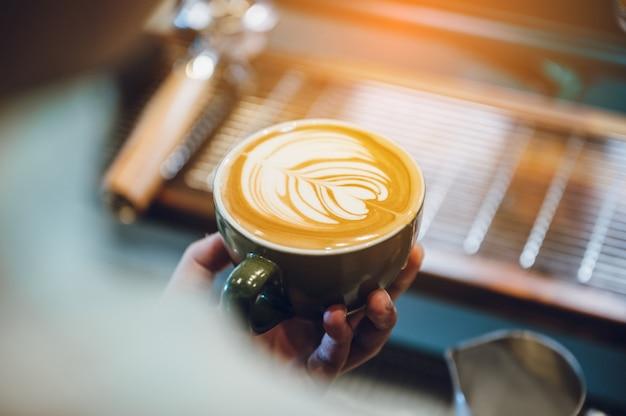 Barista che fa latte art, fuoco del colpo in tazza di latte e caffè,