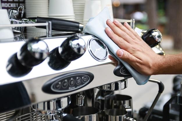 Barista uomo pulizia macchina per caffè espresso dopo la giornata lavorativa