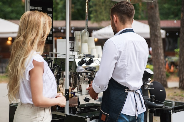 Uomo del barista che prepara il caffè per il cliente nella sua caffetteria sulla strada mobile
