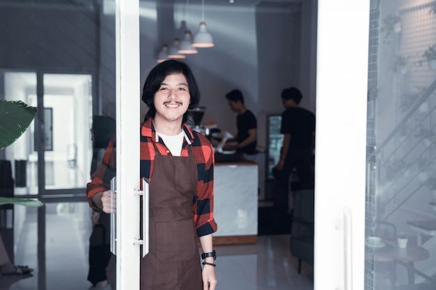 Il barista apre la porta nel suo caffè accogliente