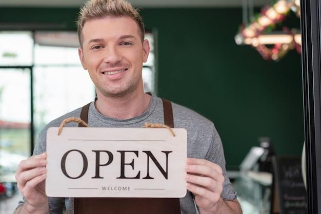 Il proprietario del barista sorride e tiene aperto il cartello di benvenuto per il cliente nella caffetteria