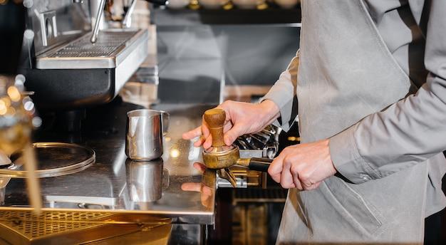 Il barista prepara il caffè in un caffè moderno.