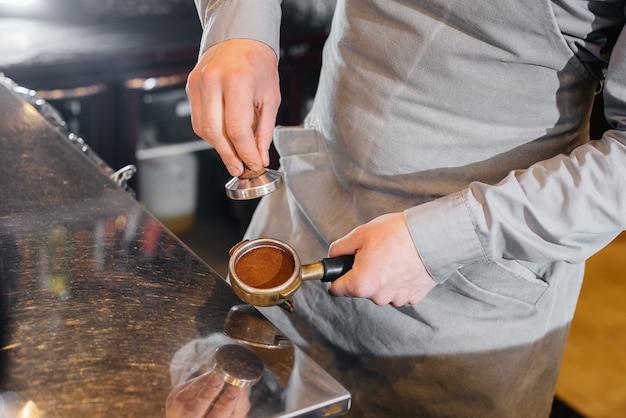 Il barista prepara un delizioso caffè in un primo piano moderno di una caffetteria.