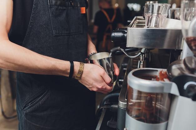 Il barista prepara il caffè espresso nella sua caffetteria.