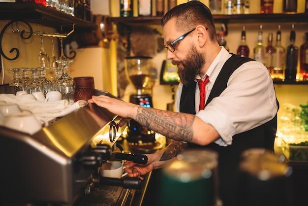 Barista che prepara il caffè nella macchina del caffè espresso