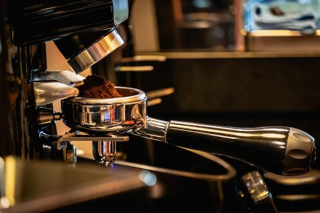Barista che prepara il portafiltro con la farina di caffè dal mulino dei chicchi di caffè