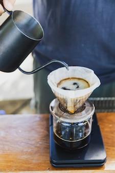 Il barista versa acqua calda prepara il caffè filtrato dalla teiera in acciaio inossidabile alla macchina per la carta gocciolante su semplici pesi neri.