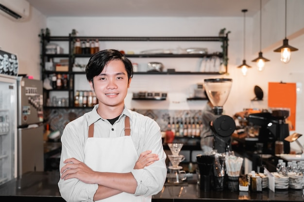 Barista in piedi con le mani incrociate davanti a una caffetteria al suo lavoro