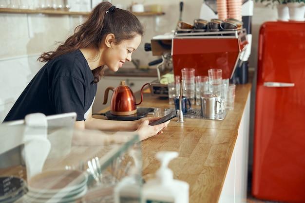 Barista che prende l'ordine dal cliente in linea sullo smartphone.