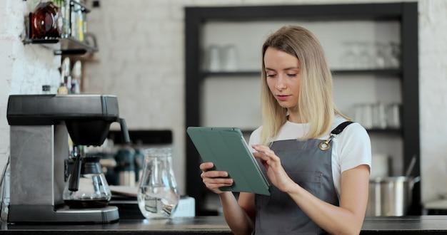 Barista con tavoletta digitale nella caffetteria. il personale femminile sta controllando i prodotti nel negozio utilizzando i tablet. concetto di caffetteria.