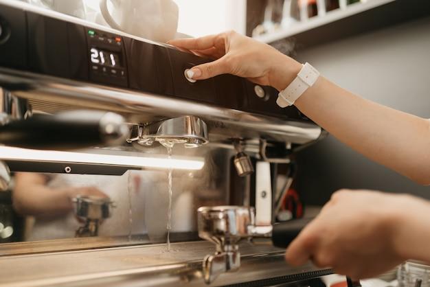 Un barista con acqua calda nella macchina per caffè espresso in una caffetteria