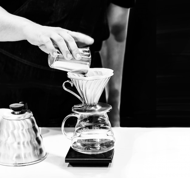 Barista che lavora in una caffetteria, close up del barista preme il caffè macinato con manomissione, barista make coffee portafilter concept