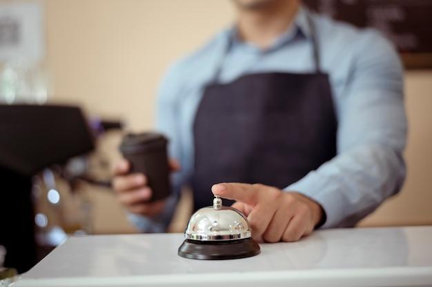 Mano del barista che prende una tazza di caffè caldo e una panetteria per offrire al cliente nella caffetteria