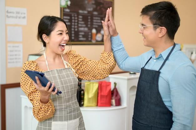 Baristi che utilizzano tablet che controllano il reddito aziendale, marketing aziendale di successo nella caffetteria