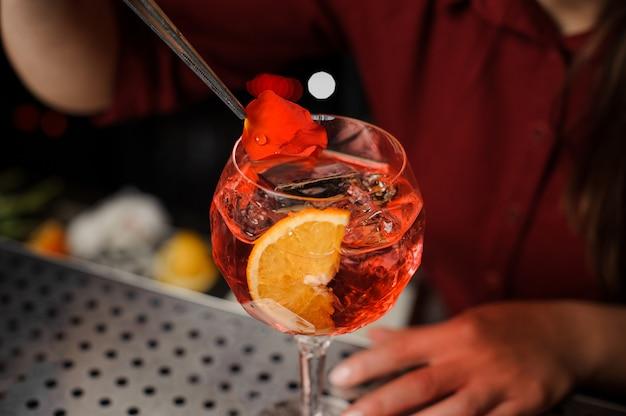 La barista termina la preparazione dello spritz veneziano, aggiungendo un petalo di rosa